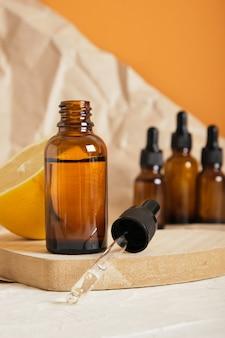 Zitronen- und braunglasflasche mit tropfer für serum oder kosmetisches öl auf einem holzpodest in herzform,