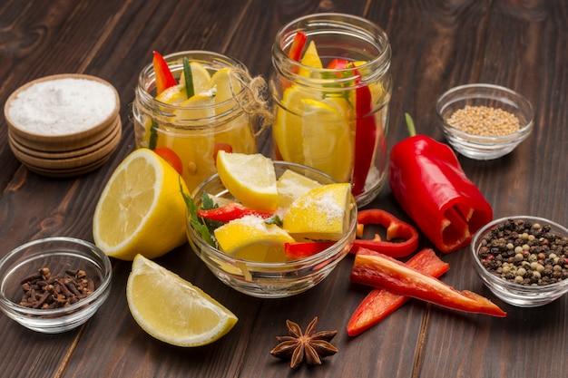 Zitronen und chili in gläsern, gewürzen und salz auf dem tisch. fermentierende produkte. natürliches heilmittel zur stärkung der immunität. draufsicht. nahansicht