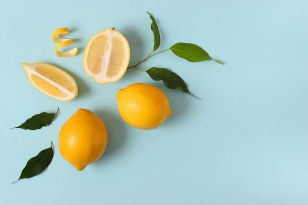 Zitronen und grüne blätter auf farbigem hintergrund. foto in hoher qualität