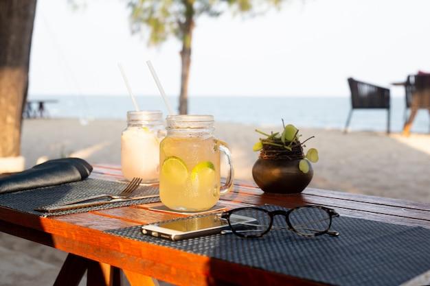 Zitronen- und honiggetränk mit scheibe des kalkes auf auffrischungssommergetränk der tabelle.