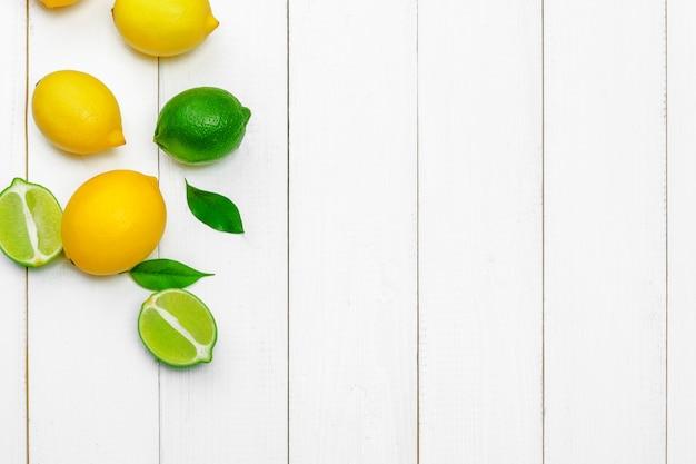 Zitronen und limetten auf einem hölzernen hintergrund.