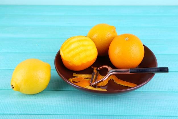 Zitronen und orangen auf teller und schälmesser auf blauer holzwand