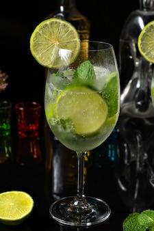 Zitronencocktail in einem glasbecher auf einem reflektierenden schwarzen hintergrund gin tonic drink mit zitrone
