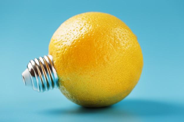 Zitronenfrucht als glühbirne auf blau.