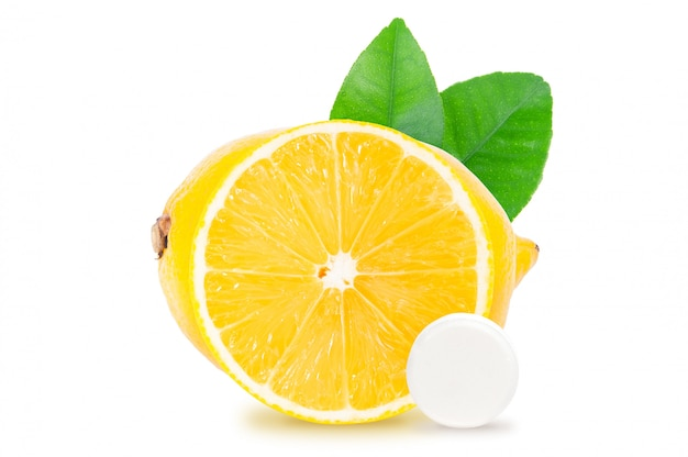 Zitronenfrucht, scheibe, grünblätter und weiße tablettenpille lokalisiert auf weißem hintergrund