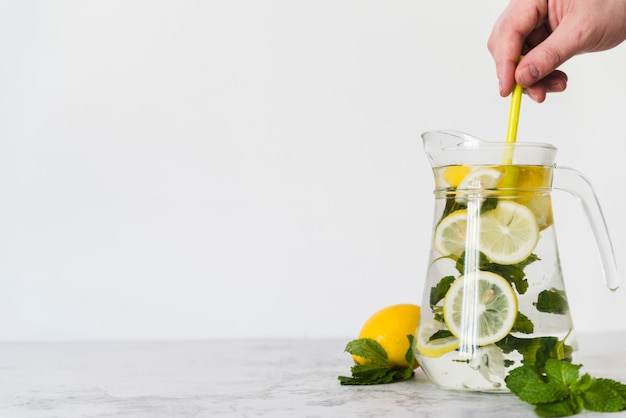 Zitronengetränk der person, das mit minze im krug rührt