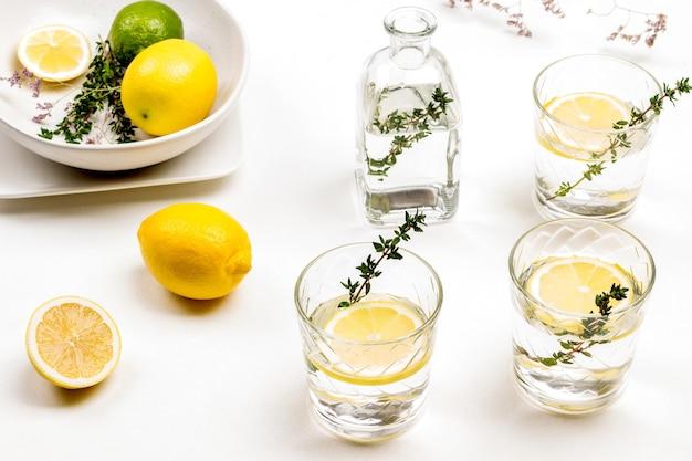 Zitronengetränk im glas. thymianzweige in glas. zitronen auf dem tisch und in der keramikschale. draufsicht.