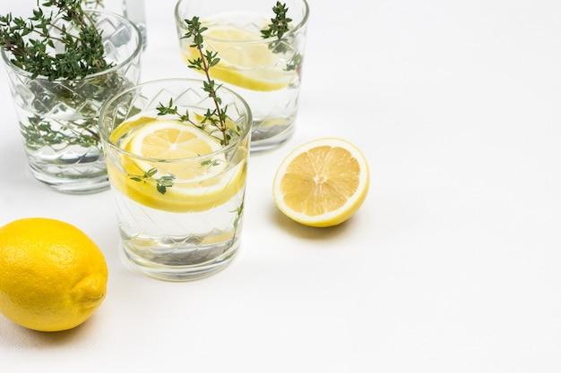 Zitronengetränk im glas. thymianzweige in glas. zitronen auf dem tisch und in der keramikschale. nahaufnahme .. draufsicht.