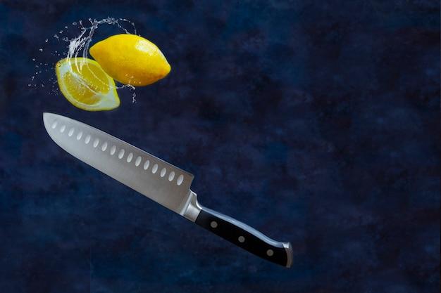 Zitronenhälften im wasserspritzer geschnitten mit fruchtmesser auf dunklem hintergrund. levitation und kopierraum