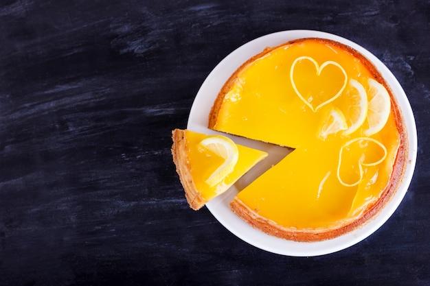 Zitronenkäsekuchen auf dem schwarzen hintergrund verziert mit zitronenschalenabschluß oben