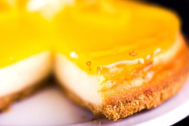 Zitronenkäsekuchen verziert mit zitronenschalenabschluß oben. selektiver fokus