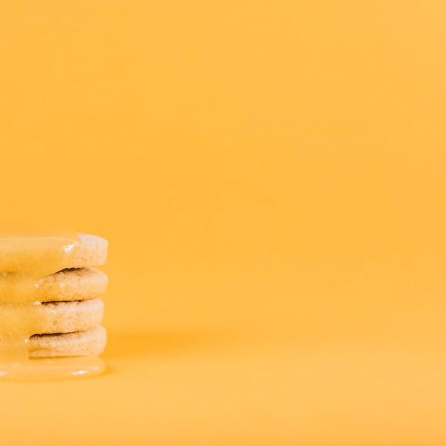 Zitronenklumpen, der über stapel frischen plätzchen auf gelber oberfläche tropft