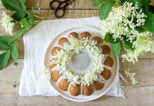 Zitronenkuchen mit einer glasur aus zucker und holunderblütensirup, dekoriert mit holunderblüten. rustikaler stil.