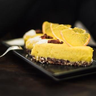 Zitronenkuchenscheibe auf behälter gegen schwarzen hintergrund