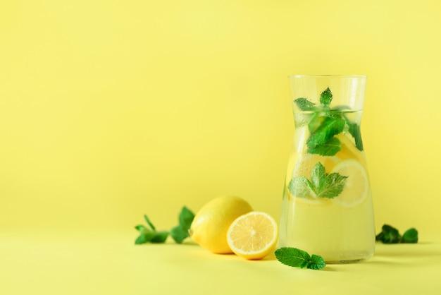Zitronenlimonade - kaltes wasser mit eis, minze, zitrone auf gelbem hintergrund. entgiftungsgetränk.