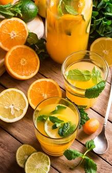 Zitronenlimonade von der frischen minze der limettenorangen in den gläsern und in der flasche, geschnittene früchte auf küchentisch