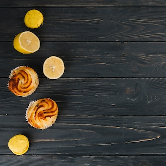 Zitronenmeringekleiner kuchen und -makronen mit halbierter zitrone auf schwarzem hölzernem strukturiertem hintergrund