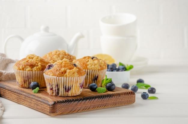 Zitronenmuffins mit blaubeeren und shtreisel mit frischen beeren auf weißem holzhintergrund. leckeres frühstück. platz kopieren.