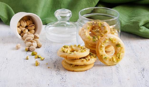 Zitronenplätzchen in form von ringen mit pistazien und zuckerglasur
