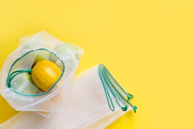 Zitronensäure in wiederverwendbaren, umweltfreundlichen netztaschen mit auf gelb