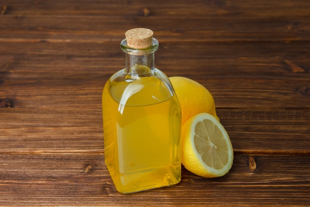Zitronensaft und zitrone mit geschnittenem zitronenhochwinkelansicht auf einem hölzernen oberflächenkopierraum für text
