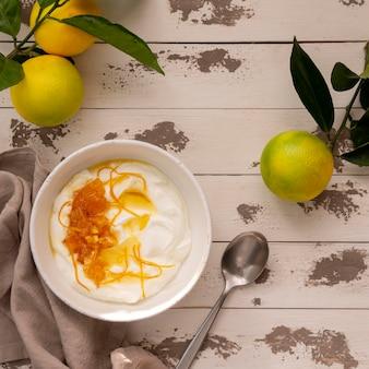 Zitronenschale mit joghurt und honig auf holztisch