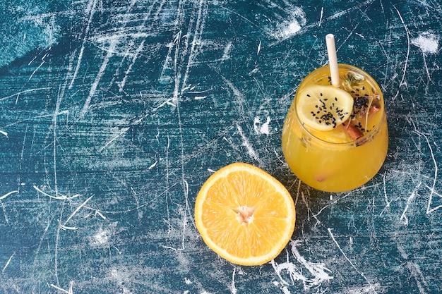Zitronenscheibe mit einer tasse getränk auf blau.