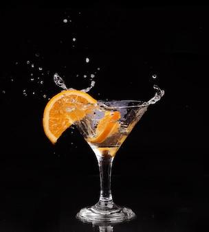 Zitronenscheibe spritzt in ein glas wasser mit einem sprühnebel von wassertröpfchen in bewegung, die in der luft über dem glas in einer dunkelheit schweben