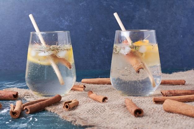 Zitronenscheibe und zimt mit einer tasse getränk auf blau.