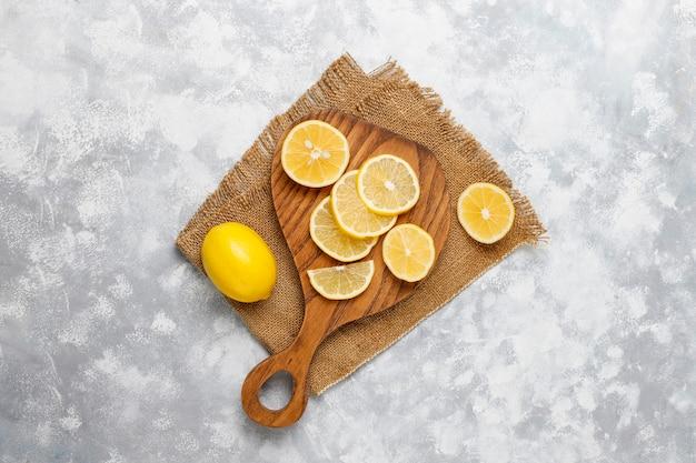 Zitronenscheiben auf schneidebrett auf beton schneiden. draufsicht, kopie, raum