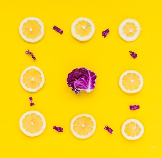 Zitronenscheiben gestalten mit purpurrotem kohl in der mitte über gelbem hintergrund