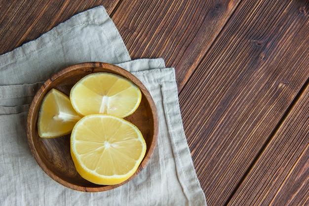 Zitronenscheiben in einem holzteller auf holz- und küchentuch. flach liegen.