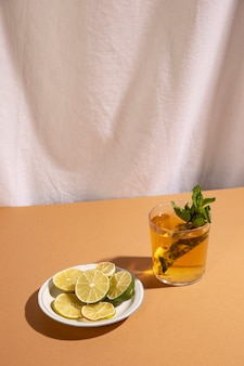 Zitronenscheiben mit cocktailgetränk über braunem schreibtisch