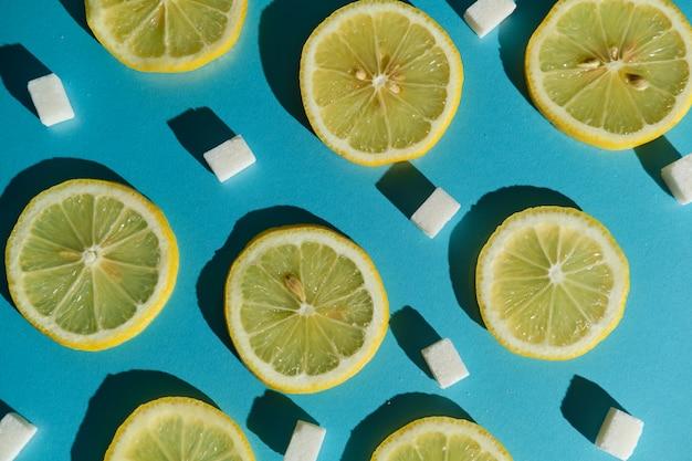 Zitronenscheiben und zuckerwürfel auf einer blauen oberfläche