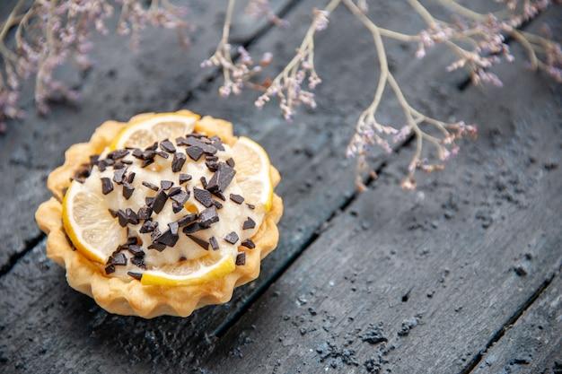 Zitronentarte von unten mit schokoladengetrocknetem blumenzweig auf dunklem tisch