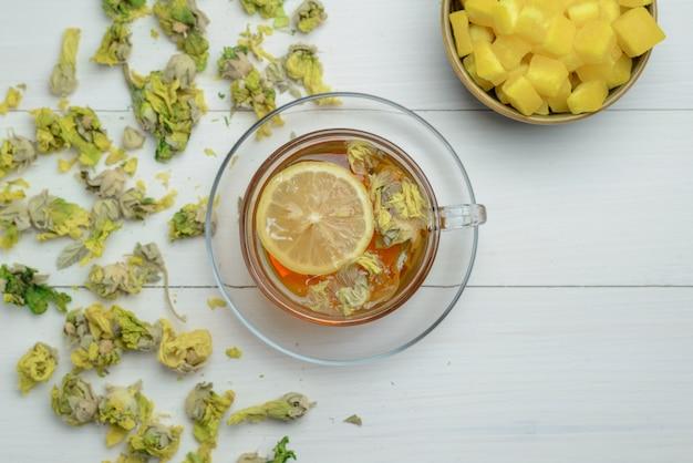 Zitronentee in einer tasse mit getrockneten kräutern, zuckerwürfel flach auf einer holzoberfläche liegend