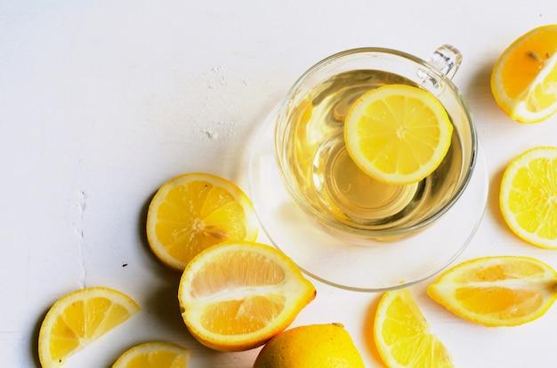 Zitronentee in einer transparenten schale auf weißem hintergrund mit scheiben der zitrone