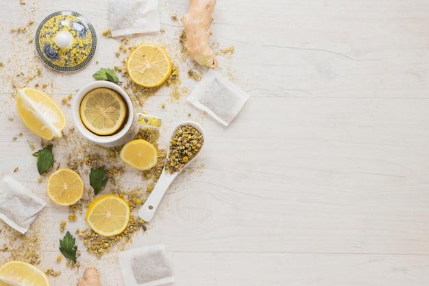 Zitronentee mit getrockneten chinesischen chrysanthemenblumen und zitronenscheiben auf holztisch