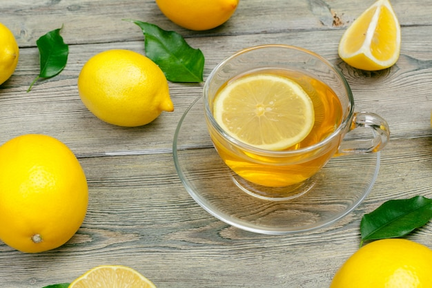 Zitronentee mit zitrone und kalk auf holztisch