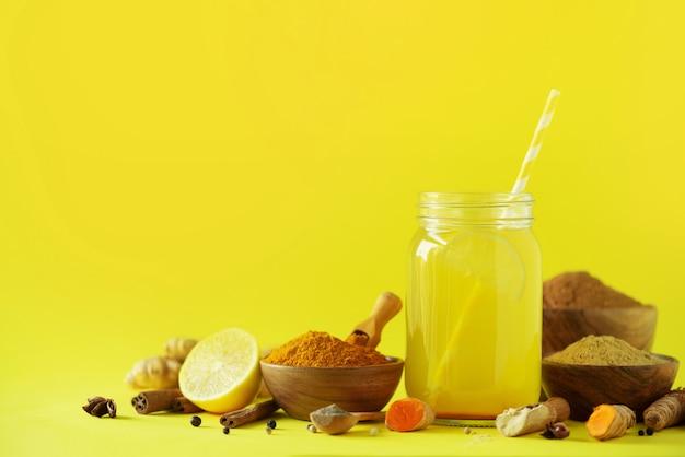 Zitronenwasser mit ingwer, kurkuma, schwarzem pfeffer. veganes heißes getränkkonzept. bestandteile für orange gelbwurzgetränk auf btight gelbem hintergrund
