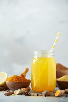 Zitronenwasser mit ingwer, kurkuma, schwarzem pfeffer. veganes heißes getränkkonzept. bestandteile für orange gelbwurzgetränk auf grauem konkretem hintergrund