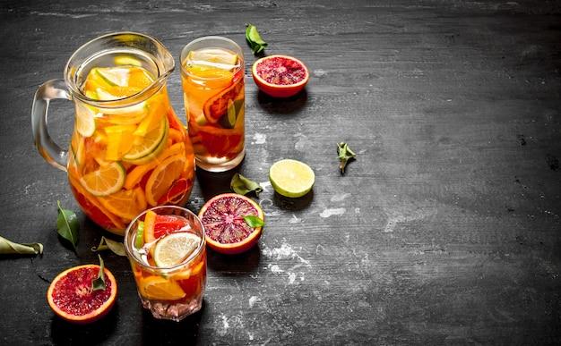 Zitrus hintergrund. frischer zitronensaft mit limettenscheiben, orangen, grapefruits und zitronen. auf schwarzer tafel.