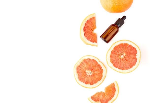 Zitrus- oder grapefruitöl in glasflasche mit frischer grapefruit auf weißem hintergrund. spa- und hautpflegeprodukt