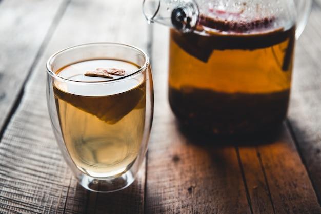 Zitrus-tee in einer transparenten teekanne und einem glas, gesundes getränk auf einem hölzernen hintergrund.