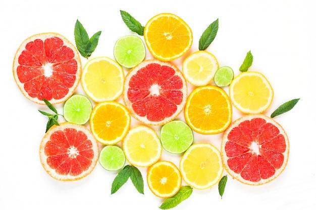 Zitrusfruchtlebensmittelmuster auf weißem hintergrund - sortierte zitrusfrüchte mit tadellosen blättern