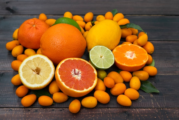 Zitrusfruchtmischorangen, -tangerinen, -zitronen und -kalk liegen auf einem schwarzen hölzernen hintergrund von den brettern.