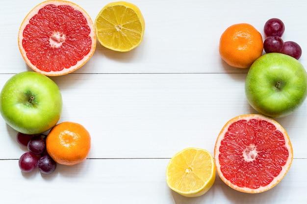 Zitrusfruchtrahmen auf dem weißen holztisch mit kopienraum