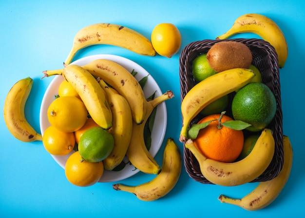 Zitrusfruchtsavocadobananen-zitronenkiwiorange in der platte und im korb auf blauer oberfläche