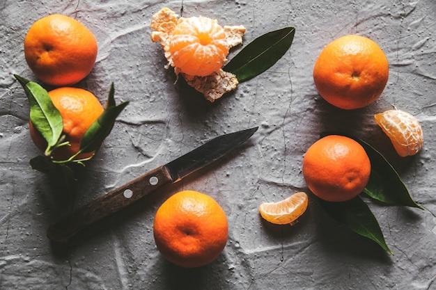 Zitrusfrüchte auf dem tisch: mandarine, mandarine mit einem messer. frische saftige bio-früchte.