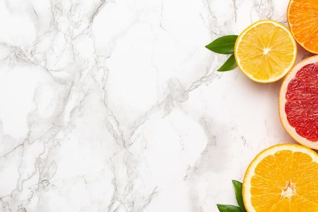 Zitrusfrüchte auf marmoroberfläche mit copyspace, frucht-flatlay, sommerliche minimalkomposition mit grapefruit, zitrone, mandarine und orange